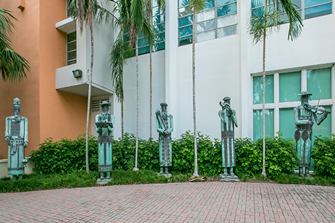 "A photograph of a sculpture collection titled, ""Five Figures."" This collection is displayed outside of the Sue and Leonard Miller Center for Contemporary Judaic Studies."